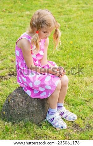 Little sad beautiful girl sitting on stone in summer city park. - stock photo