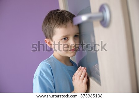 Little sad boy overhears fight of his parents through the door - stock photo