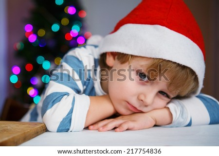 Little sad or serious child in santa hat with christmas tree and lights on background - stock photo