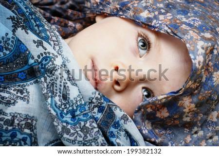 Little  sad three years old girl hidden in scarf - stock photo
