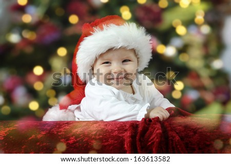little santa baby with christmas hat lying on her belly - stock photo