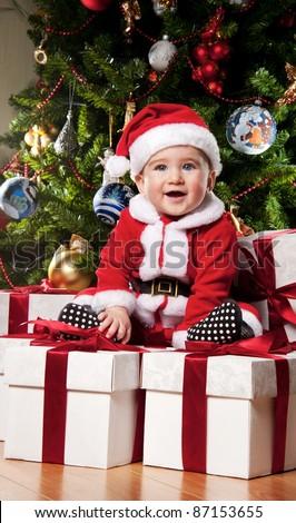 Little Santa boy sitting on a  gift boxes. - stock photo