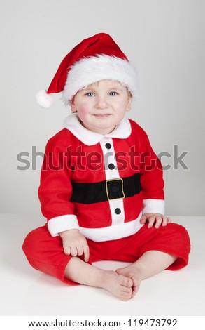Little Santa Christmas boy sitting in studio - stock photo