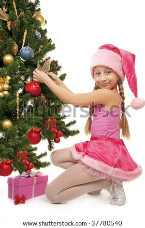 Little santa girl decorating the christmas tree - stock photo