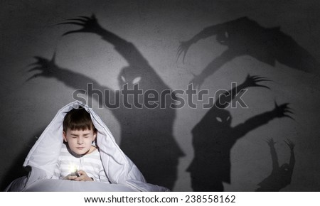 Little scared boy in bed under blanket with flashlight - stock photo