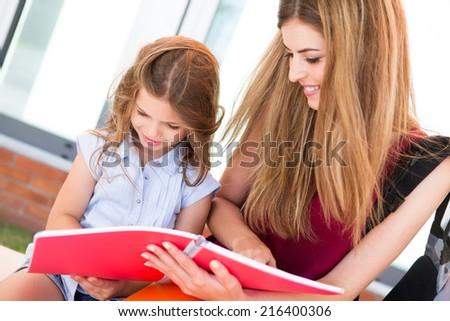 Little school girl showing sketchbook to her mother - stock photo