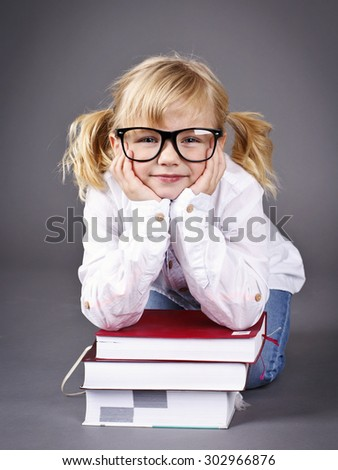 Little school girl wearing glasses and reading books - stock photo
