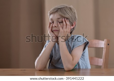 Little schoolboy at the table feeling tired - stock photo