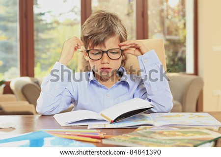 Little schoolboy bored of doing his homework at home - stock photo