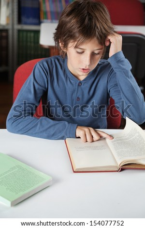 Little schoolboy reading book at table in library - stock photo
