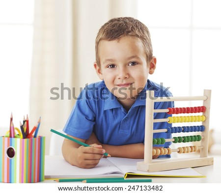Little schoolboy sitting at a desk and studying - stock photo