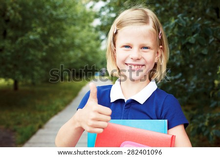 Little schoolgirl holds in hands books and smiling. She shows hand that everything is fine. - stock photo
