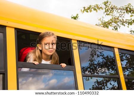 Little Schoolgirl looking through a Schoolbus Window - stock photo