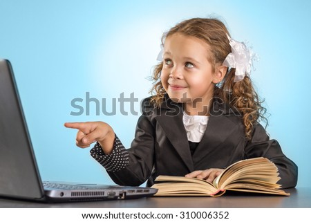 Little Schoolgirl Sits At Table With Book Shows A Finger Into The Laptop On Blue Background - stock photo