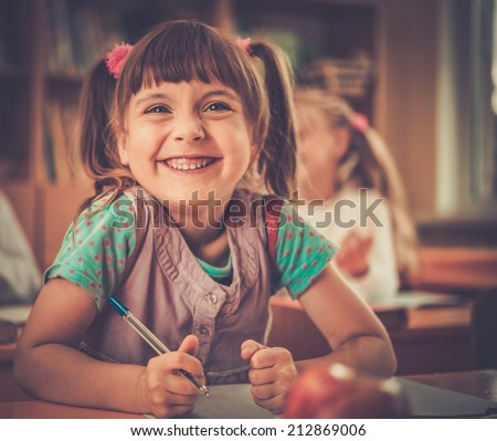 Little schoolgirl sitting behind school desk during lesson in school - stock photo