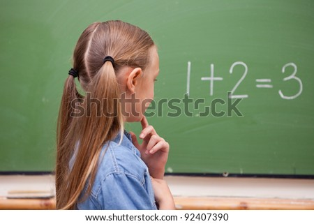 Little schoolgirl thinking while looking at the blackboard - stock photo