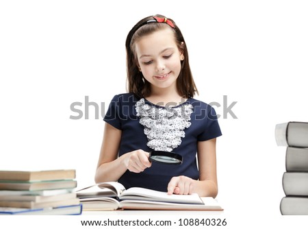Little schoolgirl wonders about interesting details in the book, isolated, white background - stock photo