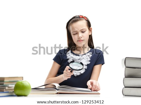 Little schoolgirl wonders about interesting material in the book, isolated, white background - stock photo