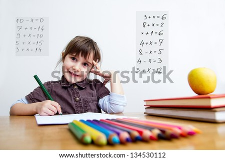 Little schoolgirl writing - stock photo