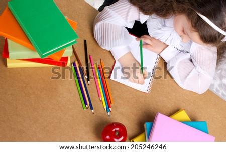 little schoolgirl writing in copybook, near lye red apple, many colorful books and pencils, top view  - stock photo