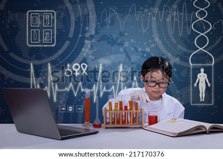 Little scientist pouring a chemical fluid into glassware to make an experiment - stock photo
