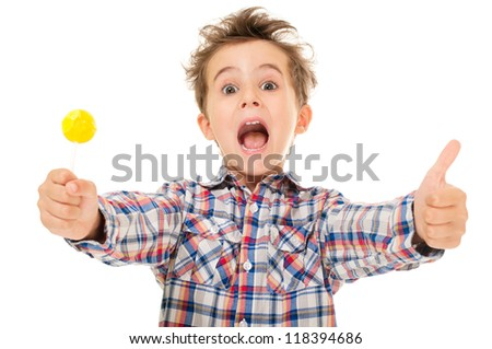 Little screaming excited boy shows thumb up with lollipop in hand  isolated on white - stock photo