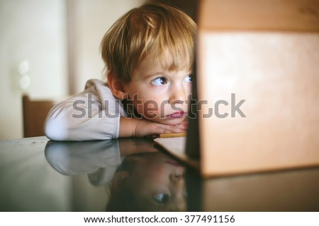 Little serious and lonely child Girl sitting and looking on tablet laptop - stock photo