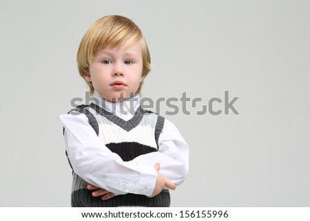 Little serious boy in vest and shirt looks away on grey background.