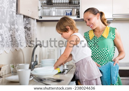 Little serious girl helping mother washing dishes in the kitchen. Focus on girl  - stock photo