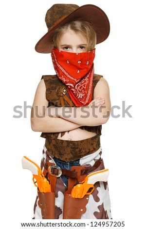 Little serious girl wearing cowboy costume and bandana covering her mouth standing with folded hands, over white background