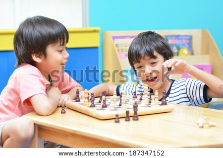Little sibling boy playing chess - stock photo