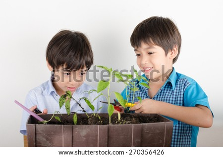Little sibling boy working with gardening together - stock photo