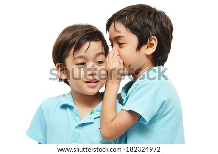 Little sibling boys sharing a secret on white background - stock photo