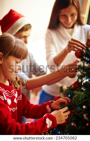 Little siblings and their mother decorating firtree for xmas - stock photo