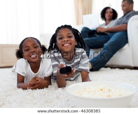 Little siblings watching television and eating pop corn in the living room - stock photo