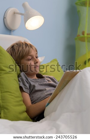 Little sick boy reading the book in his hospital bed - stock photo
