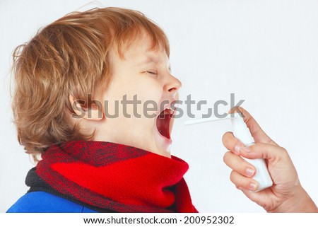 Little sick boy used medical aerosol for breath on a white background - stock photo