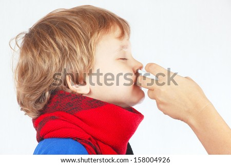 Little sick boy used nasal spray in the nose on a white background - stock photo