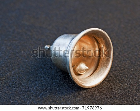 Little silver bell over black background - stock photo