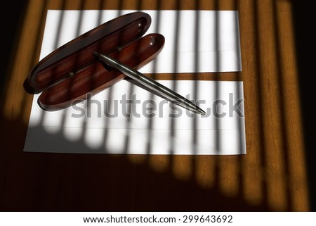 Little silver biro pen on brown wooden open case lying on two white envelopes on office table on jalousie shadow background, horizontal picture - stock photo