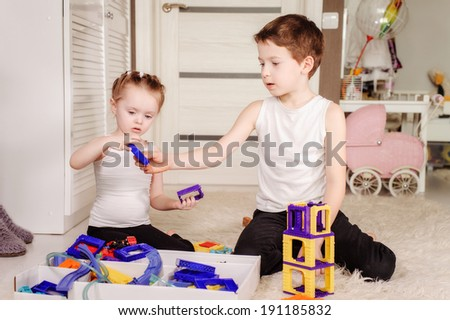 little sister and brother playing at home together - stock photo