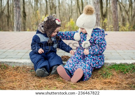 little sister hugs her toddler brother outdoors  - stock photo