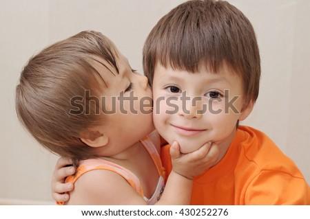 Little sister kissing older brother, Caucasian kids - stock photo