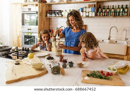 Little sisters cooking with her mother in the kitchen. Infant Chef Concept.