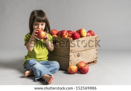 Little sitting girl eating apple with crate of apples beside her.