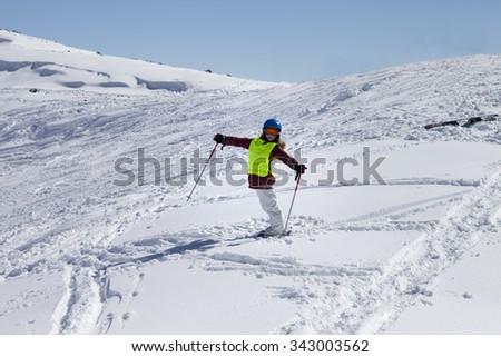 Little skier on ski slope with new fallen snow at sun day. Caucasus Mountains, Georgia, ski resort Gudauri. - stock photo