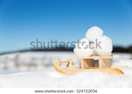 little sledge with snowballs in the snow, concept snowball fight in the winter season - stock photo