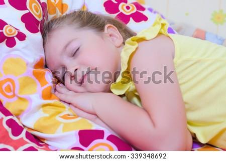 Little sleeping girl on multicolor pillow - stock photo