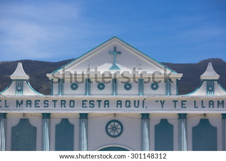 Little small blue and white small colonial church against a clear blue sky with a cross, basic decoration and letters on the facade. Merida State Venezuela - stock photo