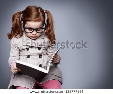 little smart girl holding a book and reading it while sitting on a stool - stock photo